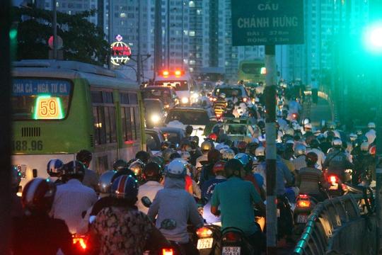 Mặc dù đèn tín hiệu đang là xanh nhưng cầu Chánh Hưng vẫn kẹt cứng. Cả hai hướng, các phương tiện ken chặt cây cầu, nối đuôi nhau nhúc nhích từng bánh xe để di chuyển.