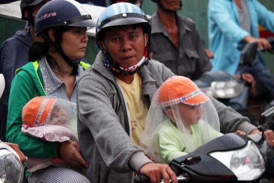 Nhiều em được bố mẹ trang bị nón và màn lưới che khói bụi, khí nóng khi phải chen chúc trong xe cộ ùn ứ.