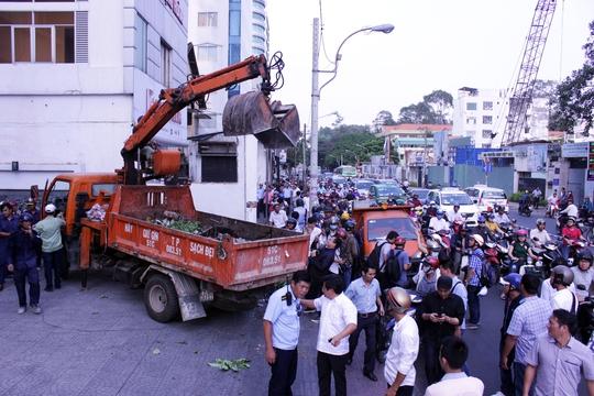 Trên đường Nguyễn Thị Minh Khai, thấy 1 bức tường và 1 bồn cây sứ trước cổng Bộ Công Thương phía Nam lấn chiếm vỉa hè, đoàn kiểm tra đập bỏ, tháo dỡ.