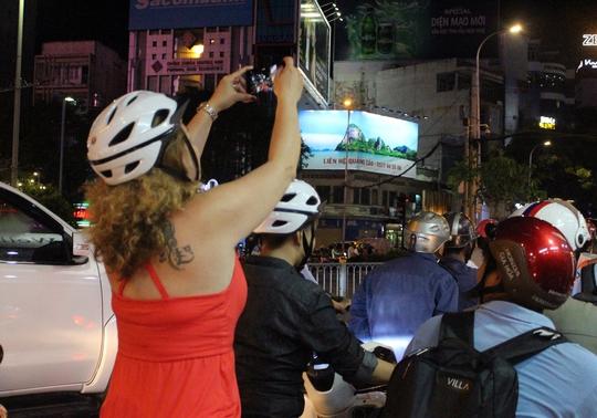 Mặc dù đang chạy xe ngoài đường, một người phụ nữ cố gắng dùng điện thoại để quay phim.