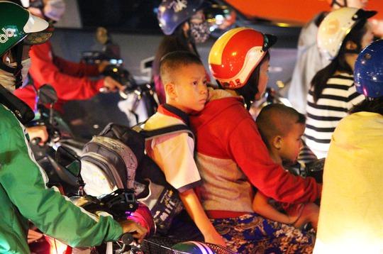 Các em nhỏ theo cha mẹ trên đường đi học về cũng phải mệt mỏi, nhiều em ngủ luôn trên xe.