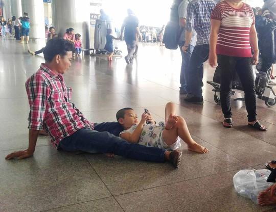 Hai cha con ngồi bệt xuống nền nhà ga bấm điện thoại trong lúc chờ đợi