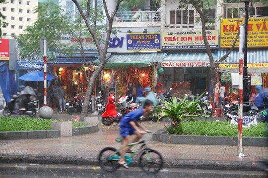 Nhiều cửa tiệm buôn bán hàng hóa ngày Tết phải tất tả dọn đồ khi mưa đổ xuống (Ảnh: H.P)