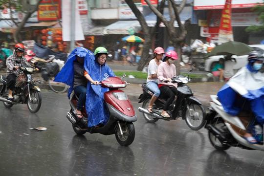 Nhiều người vội vã lưu thông trong cơn mưa chiều 25-1
