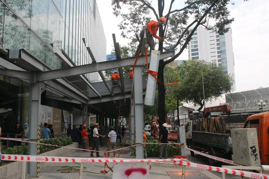 Đoàn kiểm tra thực hiện tháo dỡ mái che lấn chiếm vỉa hè của cao ốc Saigon Center.