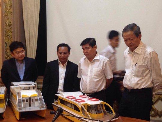 Chủ tịch UBND TP Nguyễn Thành Phong (thứ 2 từ phải sang) cùng Phó Chủ tịch UBND TP Lê Văn Khoa (bìa phải) xem mô hình tuyến buýt đường sông của Công ty TNHH Thường Nhật (Ảnh: Phan Anh)