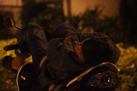 Một bác xe ôm ế khách, dựng xe ngủ chờ mưa tạnh.