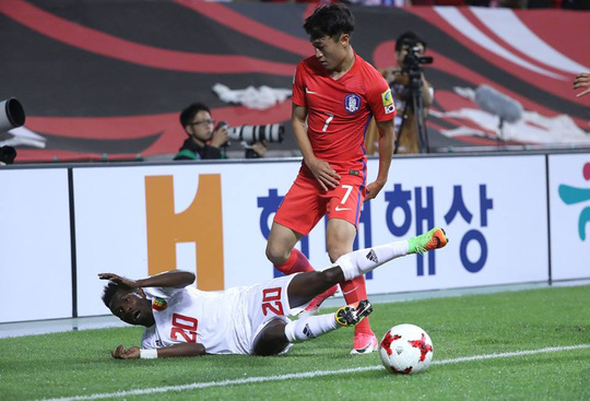 Jules Suzuki của Guinea té ngã sau pha tranh bóng với Jin-Hyun Lee của Hàn Quốc