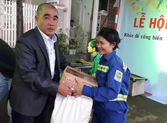 Ông Võ Văn Tân, chủ nhiệm CLB bóng đá Tâm Đức trao quà cho gia đình khó khăn