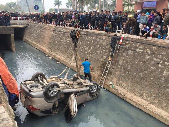 Lực lượng chức năng đang cẩu chiếc xe lên bờ