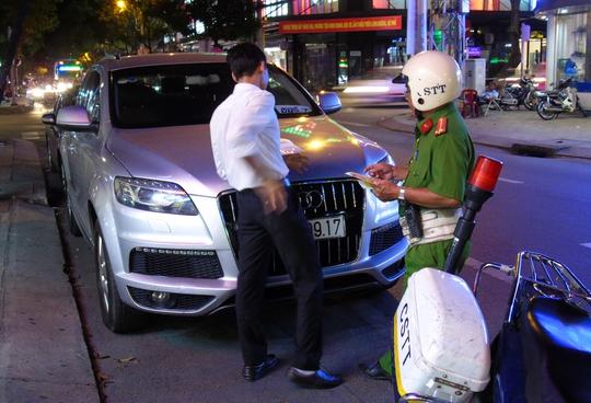 Tài xế lái chiếc xe Audi đậu trên lề đường Nguyễn Đình Chiểu bị lập biên bản xử lý.
