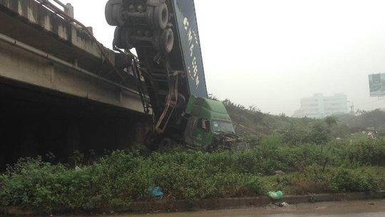 Chiếc xe container đầu kéo nằm vắt vẻo trên lan can cầu