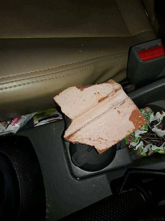Nữa viên gạch rơi thủng kính lọt vào trong ô tô - Ảnh: NVCC