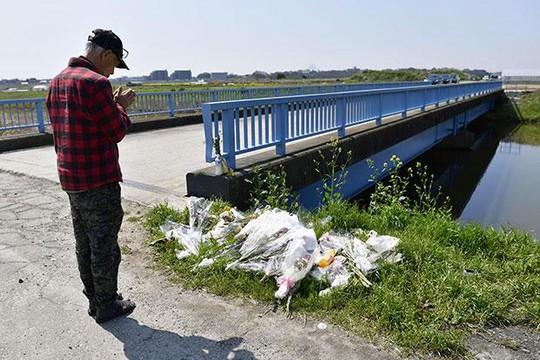 Một người đàn ông cầu nguyện hôm 14-4 tại nơi thi thể bé Nhật Linh được tìm thấy. Ảnh: KYODO NEWS