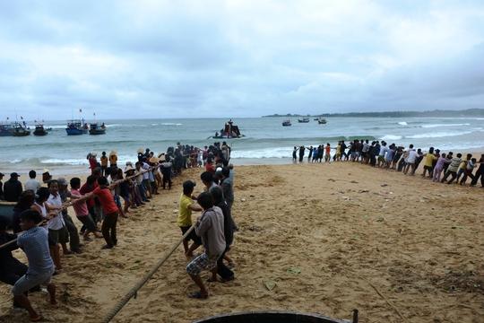 Hàng trăm người dân làng chài thôn Phước Thiện, xã Bình Hải, huyện Bình Sơn (Quảng Ngãi) tham gia cứu tàu bị sóng lớn đánh chìm. Ảnh: Tử Trực
