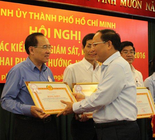 Phó Bí thư Thường trực Thành ủy TP HCM Tất Thành Cang trao bằng khen cho các tập thể, cá nhân có thành tích xuất sắc trong công tác kiểm tra, giám sát của Đảng năm 2016