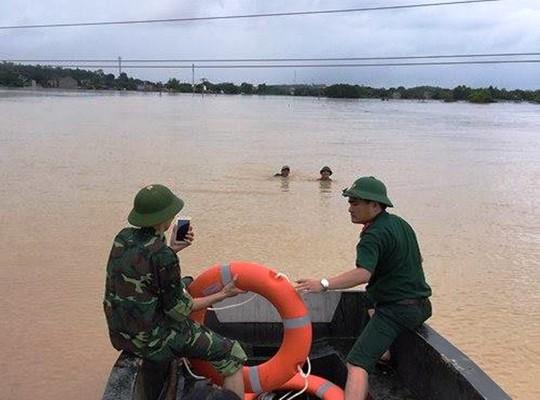 Bộ đội cứu 2 bố con đang đu dây điện giữa dòng nước lũ - Ảnh 1.