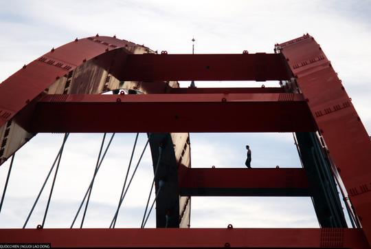 Người này liên tục di chuyển dích dắc từ các thanh ngang của cây cầu để thực hiện các thao tác mạo hiểm.