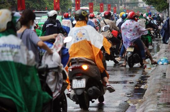 Khoảng 17 giờ ngày 2-5, một cơn mưa bất ngờ trút xuống khiến người dân chật vật chạy mưa. Trong ảnh: Nhiều người dừng lại bên đường Cộng Hòa để mặc áo mưa.