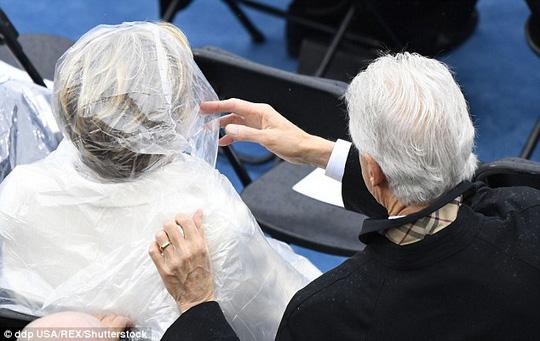 Ông Clinton chỉnh áo mưa cho vợ. Ảnh: Rex