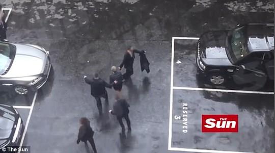 Bà Theresa May được vệ sĩ hộ tống lên xe. Ảnh: The sun