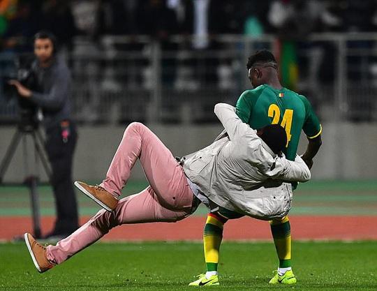 Lamine Gassama (Senegal) bị một fan cuồng ôm lấy