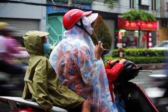 Hai em nhỏ được mẹ mặc áo mưa kỹ lưỡng trước khi tiếp tục lên đường.