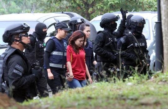 Cảnh sát áp giải Siti Aishah (áo đỏ) vào tòa. Ảnh: AP