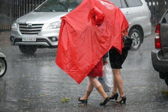 Khi mưa nhẹ hạt đi, nhiều người che chung áo mưa để về.