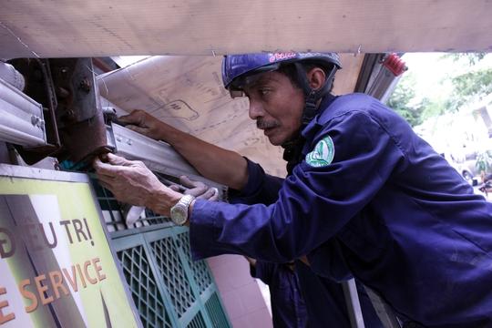 Trên đường Nguyễn Bình Khiêm, một số trường hợp vi phạm cũng bị xử lý, tịch thu đồ đạc lấn chiếm. Trong ảnh: Một công nhân đang tháo dỡ mái che một quán nước.