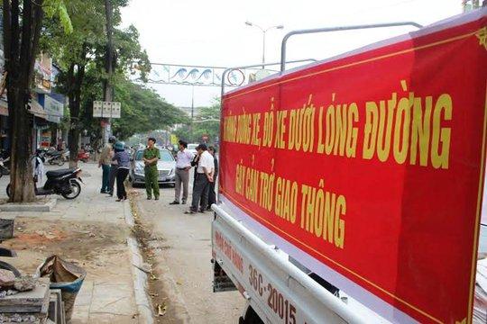 Lực lượng chức năng phường Ba Đình đang chỉ đạo tháo dỡ bảng biển lấn chiếm vỉa hè trên đường Trần Phú