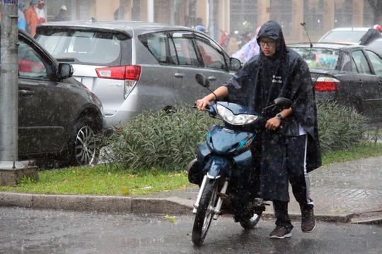 Trong cơn mưa giông, nam thanh niên dắt xe đi tìm chỗ trú.