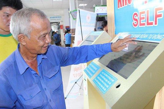 Ông Nguyễn Phú Vượng kiểm tra hồ sơ và tìm thông tin phòng khám bệnh trên máy tại Bệnh viện quận Thủ Đức