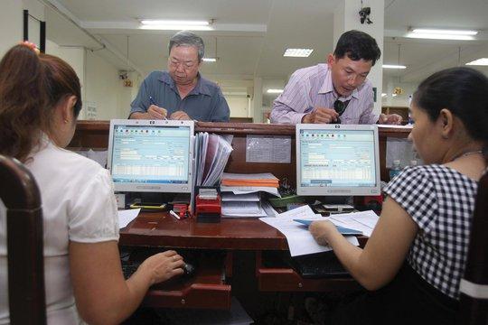 Người dân làm thủ tục tại BHXH TP HCM Ảnh: HOÀNG TRIỀU
