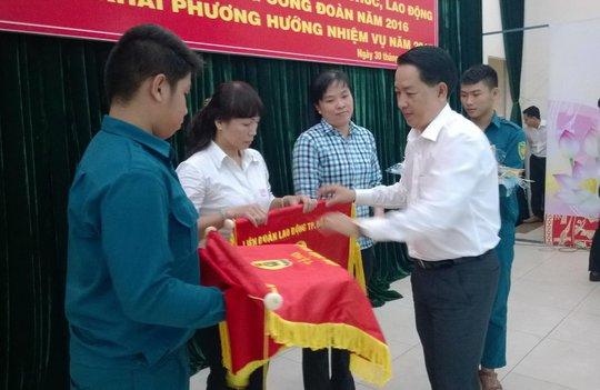 Ông Kiều Ngọc Vũ, Phó Chủ tịch LĐLĐ TP HCM, tặng cờ thi đua cho tập thể xuất sắc