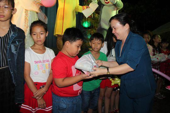 Bà Nguyễn Thị Bạch Yến, Chủ tịch LĐLĐ quận Gò Vấp, trao quà cho con công nhân Ảnh: THANH NGA