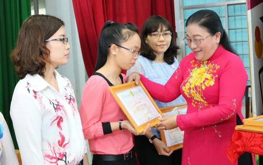Bà Nguyễn Thị Bích Thủy, Phó Chủ tịch LĐLĐ TP HCM, trao bằng khen cho các nữ CNVC-LĐ đạt thành tích 2 giỏi Ảnh: MAI CHI