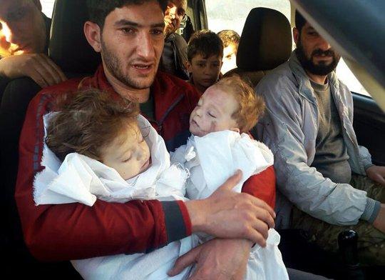 Anh Abdel Hameed Alyousef đau đớn ôm thi thể 2 con trong tay. Ảnh: AP
