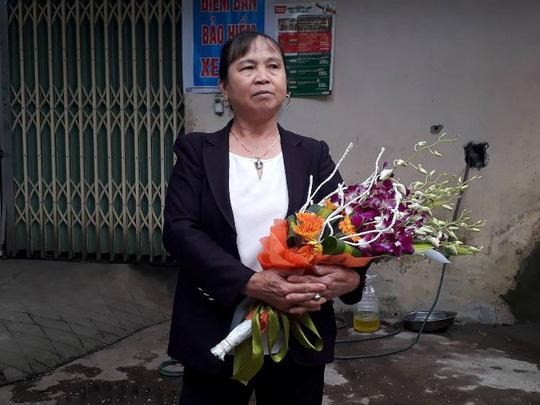 Một phụ nữ ôm hoa chờ đoàn đại biểu đến tặng