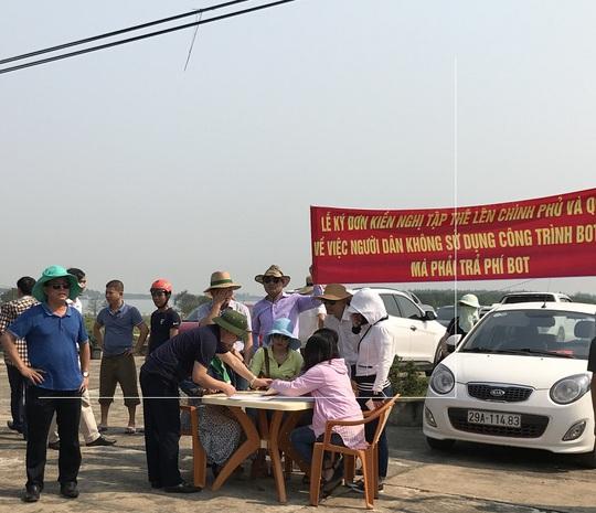 Bất chấp trời nắng nóng, nhiều người dân vẫn tập trung ký kiến nghị yêu cầu không được thu phí của người dân không sử dụng đường BOT.