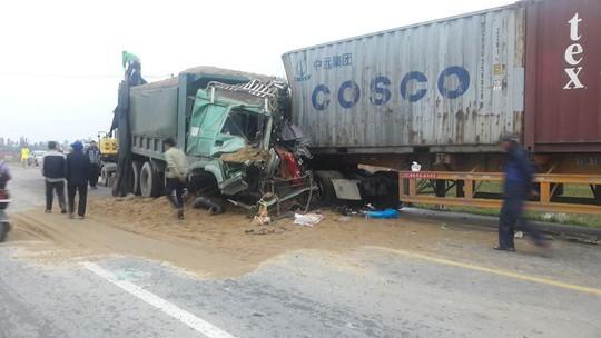 Xe tải đấu đầu xe container, 2 tài xế kẹt trong cabin bẹp dúm - Ảnh 1.