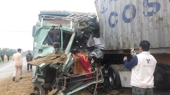 Xe tải đấu đầu xe container, 2 tài xế kẹt trong cabin bẹp dúm - Ảnh 2.