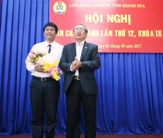 Ông Nguyễn Hoà, Chủ tịch LĐLĐ tỉnh Khánh Hoà (phải) tặng hoa chúc mừng ông Bùi Thanh Bình