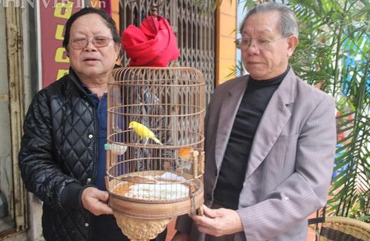 Chủ tịch Hội chim Yến Hà Nội Vũ Xuân Quyết (bên trái) và đồng môn nâng niu một chú chim Hoàng Yến có giá gần chục triệu đồng