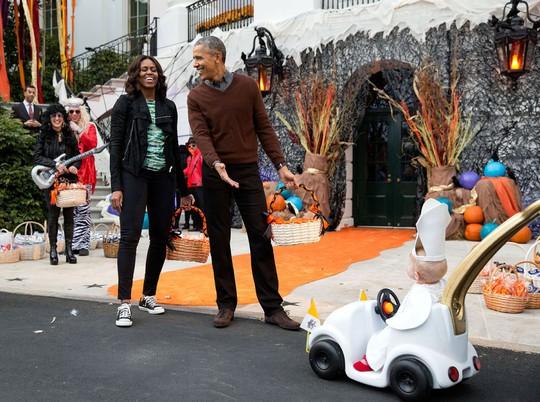 Vợ chồng ông Obama thích thú trước em bé hóa trang thành Giáo hoàng dịp lễ Halloween năm 2015. Ảnh: Pete Souza—The White House