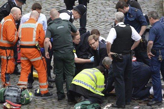 Mọi người đang cố cứu cảnh sát Palmer trước khi anh chết. Trong số người cứu hộ có nghị sĩ đảng Bảo thủ Tobias Ellwood (đeo kính). Ông được ca ngợi là người hùng nhờ từ văn phòng lao thẳng ra ngoài sơ cứu người bị thương, bất chấp cảnh sát yêu cầu mọi người ở yên hoặc sơ tán. Ảnh: AP