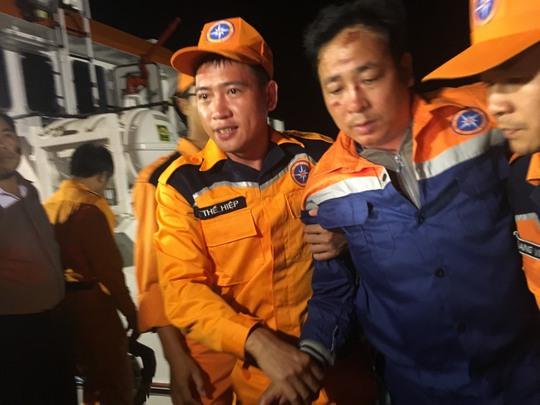 Thuyền trưởng tàu Hải Thành 26-BLC Nguyễn Viết Thắng (thứ 2 từ phải sang) được đưa lên xe cứu thương Ảnh: NGỌC GIANG