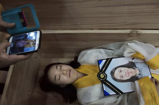 Học viên ôm di ảnh nằm trong quan tài một lễ tang giả tại Trung tâm Hàn gắn Seoul Hyowon Ảnh: AGENCE VU