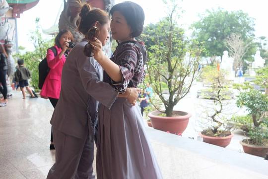 Phật tử mang thêm váy choàng che phủ đến gót chân cho nữ du khách mặc váy