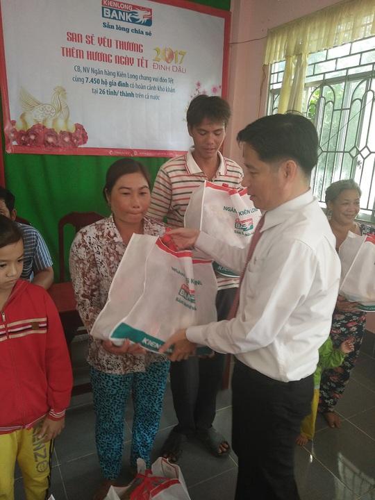 Đại diện Kienlongbank (bên phải) tặng quà Tết cho bà con (Ảnh: Tấn Thành)